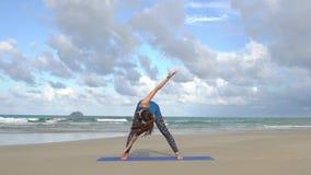 Utbildning för ung kvinna på stranden framme av havet Gymnastiska övningar för morgon Sunt aktivt livsstilbegrepp arkivfilmer