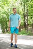 Utbildning för utomhus- sport Stilig man i sportkläder som går på naturligt landskap Övande sport för idrotts- idrottsman royaltyfri foto