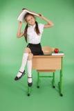 Utbildning, folk, barn och skolabegrepp - barnet skolar flickasammanträde på skrivbordet med en bok på hennes huvud Royaltyfria Foton