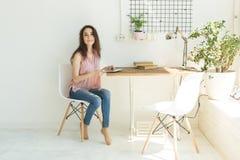 Utbildning, folk och teknologibegrepp - ung studentkvinna som hemma använder den digitala minnestavlan royaltyfri bild