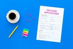 utbildning higher Högskolaansökningsblankett som är klar att fylla nära kaffekoppen och brevpapper på bästa sikt för blå bakgrund arkivbild