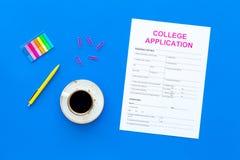 utbildning higher Högskolaansökningsblankett som är klar att fylla nära kaffekoppen och brevpapper på bästa sikt för blå bakgrund royaltyfri foto