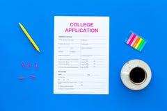 utbildning higher Högskolaansökningsblankett som är klar att fylla nära kaffekoppen och brevpapper på bästa sikt för blå bakgrund arkivfoto