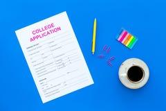 utbildning higher Högskolaansökningsblankett som är klar att fylla nära kaffekoppen och brevpapper på bästa sikt för blå bakgrund arkivbilder