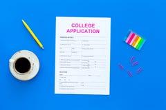 utbildning higher Högskolaansökningsblankett som är klar att fylla nära kaffekoppen och brevpapper på bästa sikt för blå bakgrund royaltyfria bilder