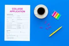 utbildning higher Högskolaansökningsblankett som är klar att fylla nära kaffekoppen och brevpapper på bästa sikt för blå bakgrund royaltyfria foton