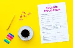 utbildning higher Högskolaansökningsblankett som är klar att fylla nära kaffekoppen och brevpapper på bästa sikt för gul bakgrund arkivbilder