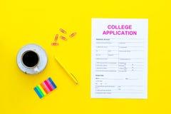 utbildning higher Högskolaansökningsblankett som är klar att fylla nära kaffekoppen och brevpapper på bästa sikt för gul bakgrund royaltyfria bilder
