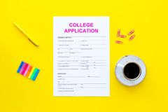 utbildning higher Högskolaansökningsblankett som är klar att fylla nära kaffekoppen och brevpapper på bästa sikt för gul bakgrund arkivfoto