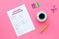 utbildning higher Högskolaansökningsblankett som är klar att fylla nära kaffekoppen och brevpapper på bästa sikt för rosa bakgrun royaltyfri foto