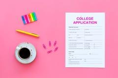 utbildning higher Högskolaansökningsblankett som är klar att fylla nära kaffekoppen och brevpapper på bästa sikt för rosa bakgrun arkivfoto