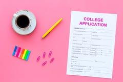 utbildning higher Högskolaansökningsblankett som är klar att fylla nära kaffekoppen och brevpapper på bästa sikt för rosa bakgrun royaltyfria foton