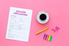 utbildning higher Högskolaansökningsblankett som är klar att fylla nära kaffekoppen och brevpapper på bästa sikt för rosa bakgrun royaltyfri bild