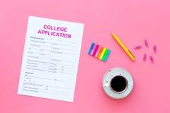 utbildning higher Högskolaansökningsblankett som är klar att fylla nära kaffekoppen och brevpapper på bästa sikt för rosa bakgrun royaltyfria bilder