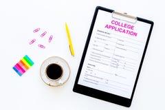 utbildning higher Högskolaansökningsblankett som är klar att fylla nära kaffekoppen och brevpapper på bästa sikt för vit bakgrund royaltyfri foto