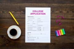 utbildning higher Högskolaansökningsblankett som är klar att fylla nära kaffekoppen och brevpapper på mörk träbakgrundsöverkant royaltyfria bilder