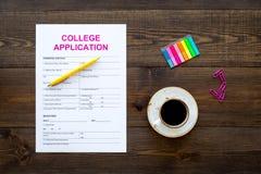 utbildning higher Högskolaansökningsblankett som är klar att fylla nära kaffekoppen och brevpapper på mörk träbakgrundsöverkant fotografering för bildbyråer