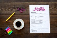 utbildning higher Högskolaansökningsblankett som är klar att fylla nära kaffekoppen och brevpapper på mörk träbakgrundsöverkant arkivbilder