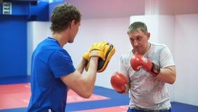 Utbildning i den boxas idrottshallen Medelåldersa slag för en idrottsman nen i boxninghandskar med hans lagledare stock video