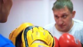 Utbildning i den boxas idrottshallen Medelåldersa slag för en idrottsman nen i boxninghandskar med hans lagledare arkivfilmer