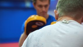 Utbildning i den boxas idrottshallen Medelåldersa slag för en idrottsman nen i boxninghandskar med hans lagledare lager videofilmer