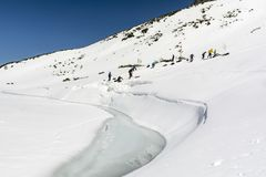 Utbildning i vinterturism på en djupfryst sjö i de Tatra bergen Simulering av den fallande partnern in i glaciärsprickan och puen Royaltyfri Foto