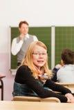 Utbildning - lärare med eleven i skolateaching Royaltyfri Foto