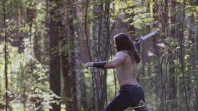 Utbildning med en kniv i hans händer i den autentiska tjocka historiska atmosfären för skog mycket stock video