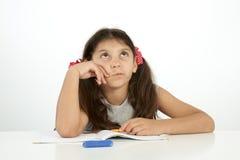 Utbildning och skolabegrepp en flicka som försöker att finna svaret Royaltyfri Fotografi