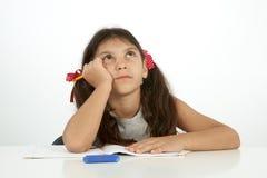 Utbildning och skolabegrepp en flicka som försöker att finna svaret Fotografering för Bildbyråer