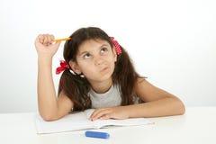 Utbildning och skolabegrepp en flicka som försöker att finna svaret Arkivbild