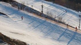 Utbildning på skidalutningen i staden Aktiva vintersportar Folket går ner kullen skidar på och snowboards _ arkivfilmer