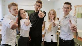 Utbildningsbegrepp - lyckligt lag av studenter som visar upp tummar på skolan arkivfoton