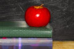 Utbildningsbegrepp med äpplet på bunt av böcker på svart tavlabac arkivfoton