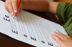 Utbildningsbegrepp med barnet som lärer att skriva Arkivfoto