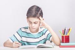 Utbildningsbegrepp med den bekymrade skolapojken royaltyfri bild