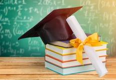 Utbildningsbegrepp med locket och böcker på trä royaltyfria bilder