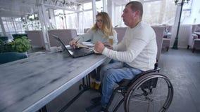Utbildningskurser för handikappade personer, mogna män för den smarta mörbultade studenten i rullstol med handleder kvinnligt und stock video