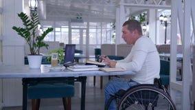 Utbildningsonline- ogiltig man i hjulstol som talar genom att använda bärbar datordatoren som sitter på tabellen med böcker och k lager videofilmer