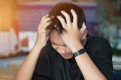 Utbildningsprovbegrepp: Asiatisk pojkestudent som studerar stressade huvudvärker för examina i klassrum som lär kurser som gör si arkivfoton