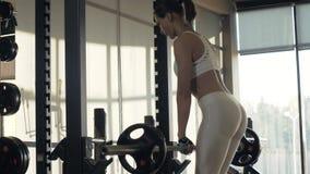 Utbildningssluttning för ung kvinna med konditionutrustningframdelen av spegeln på idrottshallklubban lager videofilmer