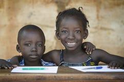 Utbildningssymbol: Par av afrikanska barn som ler på skolan Arkivfoto