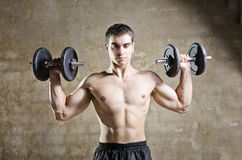 Utbildningsvikter för ung man i gammal idrottshall Royaltyfria Foton