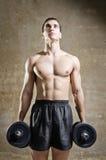Utbildningsvikter för ung man i gammal idrottshall Royaltyfri Fotografi