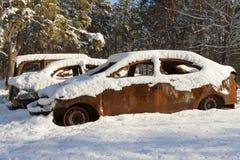 Utbrända bilar som täckas i snö Fotografering för Bildbyråer