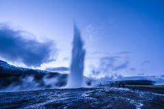 Utbrott av den Strokkur geyseren i Island Kalla färger för vinter, månebelysning till och med natt royaltyfri fotografi