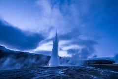 Utbrott av den Strokkur geyseren i Island Kalla färger för vinter, månebelysning till och med natt arkivfoto