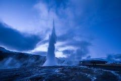 Utbrott av den Strokkur geyseren i Island Kalla färger för vinter, månebelysning till och med natt royaltyfri bild