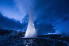 Utbrott av den Strokkur geyseren i Island Kalla färger för vinter, månebelysning till och med natt fotografering för bildbyråer