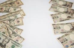 Utbyt pengarbegreppet, högen av USA-sedlar på det vänstert och högen av japanska sedlar på rätt arkivfoton